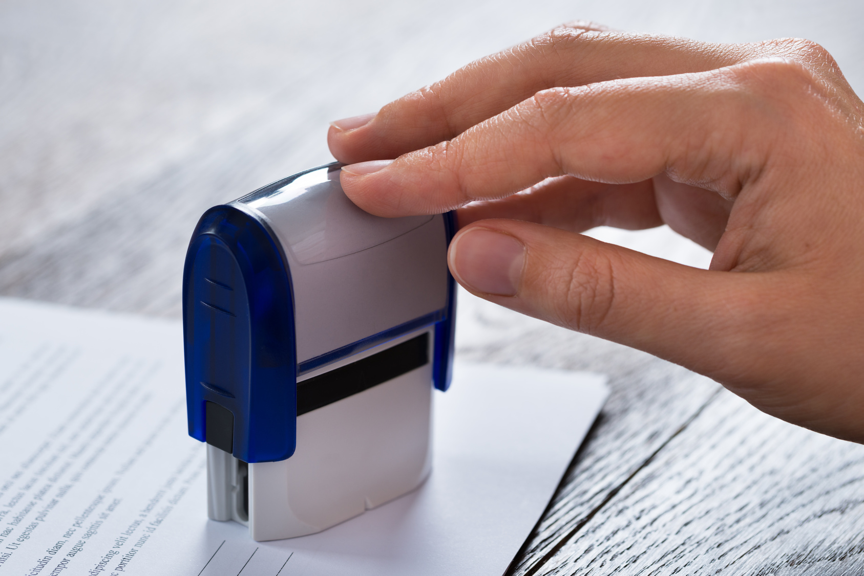 Close-up Of Person Hands Pressing Stamper On Document