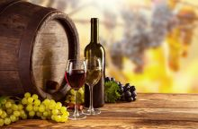Red and white wine bottle and glass on wooden keg. Grapes of wine on background